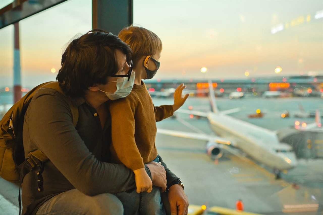 Dad and son wearing masks and looking out of an airport window.
